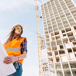 жена гледа чертеж а на заден план строяща се сграда